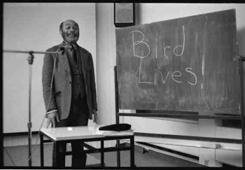 Ted Joans writing BIRD LIVES in Hamburg; photo copyright Michael Kellner